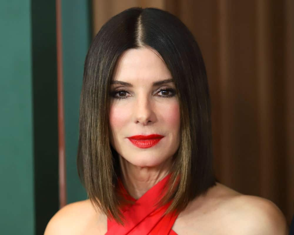 Straightforward and trouble-free, this hairstyle for women with short straight hair is sported by the legendary Sandra Bullock. Notice how a slightly tilted lob coupled with soft caramel highlights in ultra sleek deep brown hair make her look effortlessly stylish.