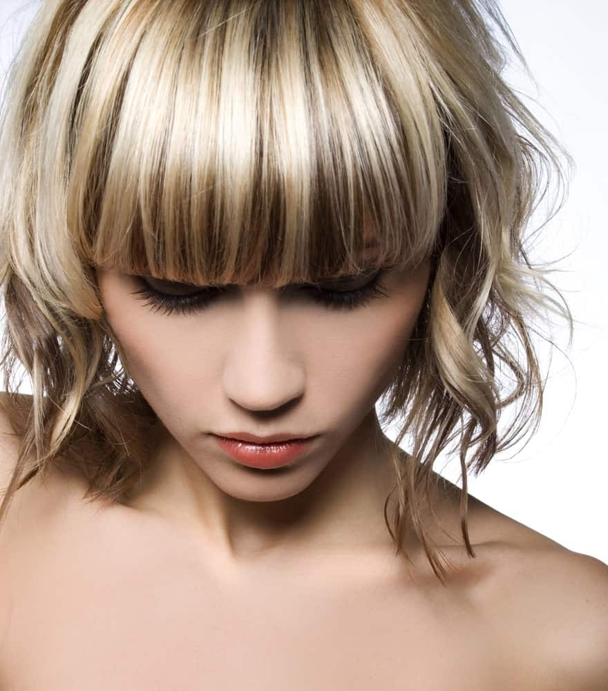 This hair color and style works perfectly for those looking for more subtle hair color. The combination of highlights and lowlights, coupled with full front bangs and curly, chin-length hair creates a soft look that is just as classy as it is trendy.