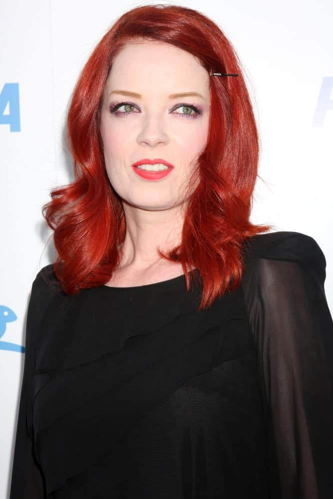 Sometimes even a single hairclip and loose, bouncy curls can make a hairstyle truly chic for women with short red hair.