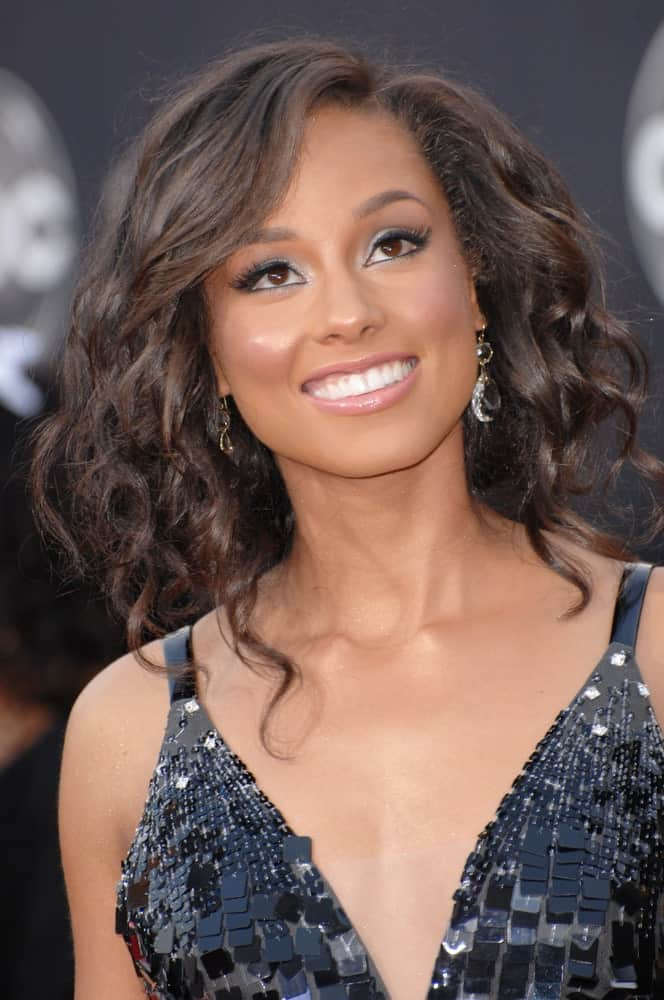 Alicia Keys short hairstyle for women with curly hair evokes poise and charm with the perms highlighted by a bob cut and deep side-swept bangs.