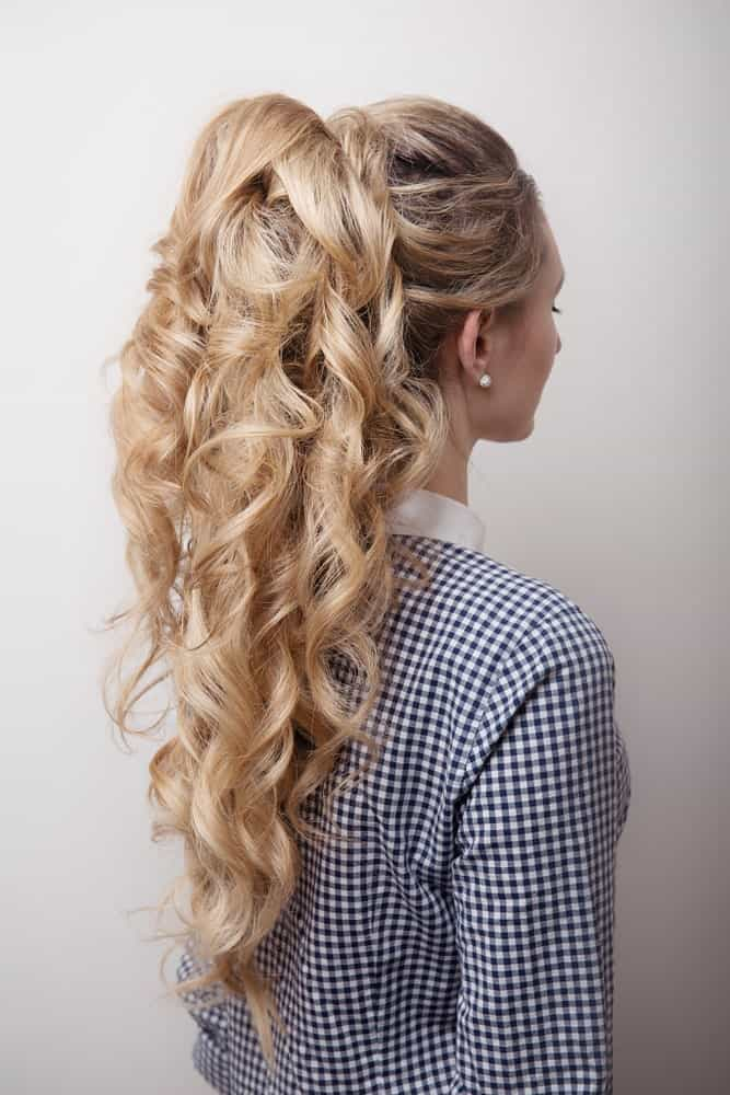 Featuring long, curly blonde hair with lowlights tied in a high ponytail – this hairstyle is truly a classic. While the curls add texture to the hair, the lowlights take the entire look to the next level.
