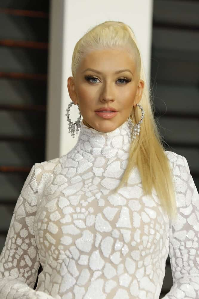 This diva is always giving her fans absolutely funky and crazy hair goals all the time. Christina Aguilera looks super stylish with her straight blonde hair pulled all the way back into a stiff pony-tail with slightly poofed up hair in the front to give it a little texture.