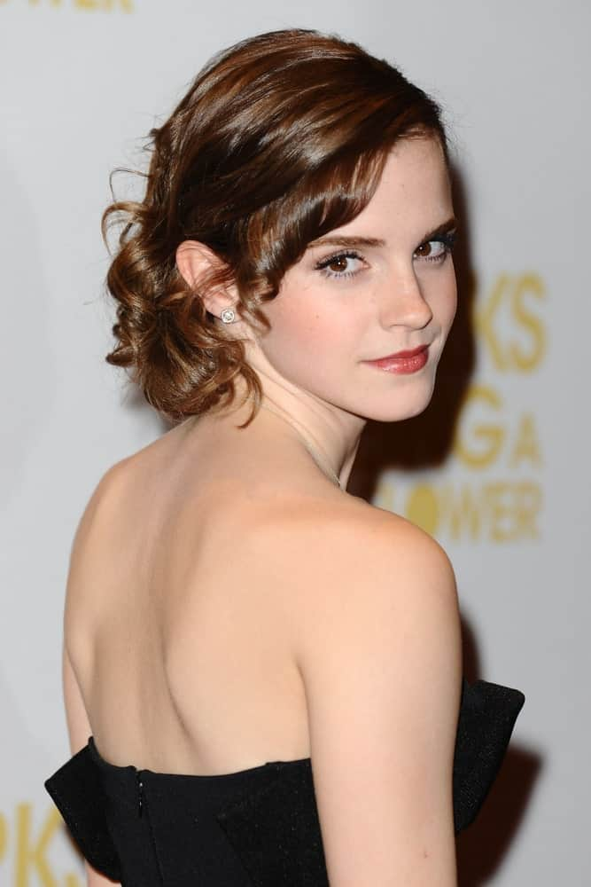 Emma Watson looks like a dream come true in her beautiful short hairstyle. All her hair has been pinned towards the back except from one side where knotted ringlets of small strands of hair have been let loose near the forehead.