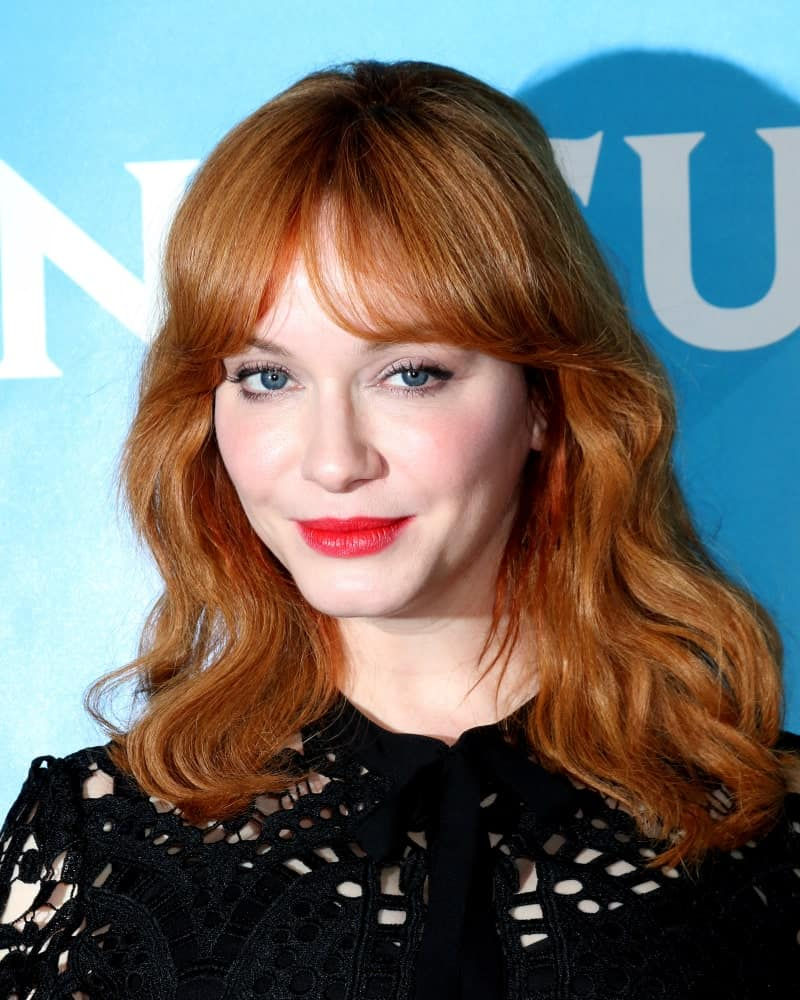 Natural redhead Christina Hendricks sports this uncomplicated hairstyle for women with slightly curled hair type. Curtain-style center-parted bangs coupled with curly hair divided and sported on both shoulder will look intense despite the simplicity if you have eye-catching auburn hair like hers.