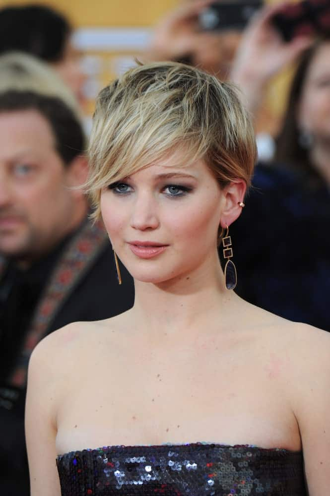 Jennifer Lawrence never takes it easy with her hair and always seems to come back with a bang with her usually crazy and funky hair looks. Here she is again with an amazing pixie cut that has shades of black on the underneath followed by golden-ashy highlights over the crown of her head. This is best described as stunning and extraordinary.