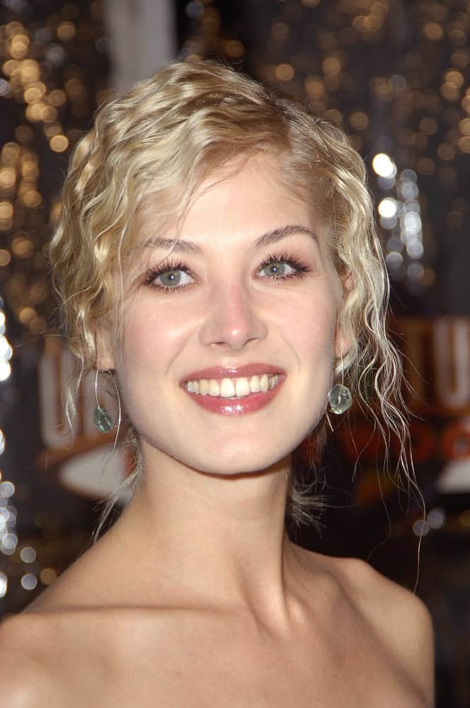 Anyone who loves experimenting with their hair would love this super bold and out-there kind of a hairdo. This is Rosamund Pike rocking this 90's kind of a hairdo with a middle parting and super small, tight waves that almost look like curls. All the hair has been swept towards the back, so it is an ideal hairstyle for someone who wants to flaunt their waves and curls yet tie them up in knots or twists.