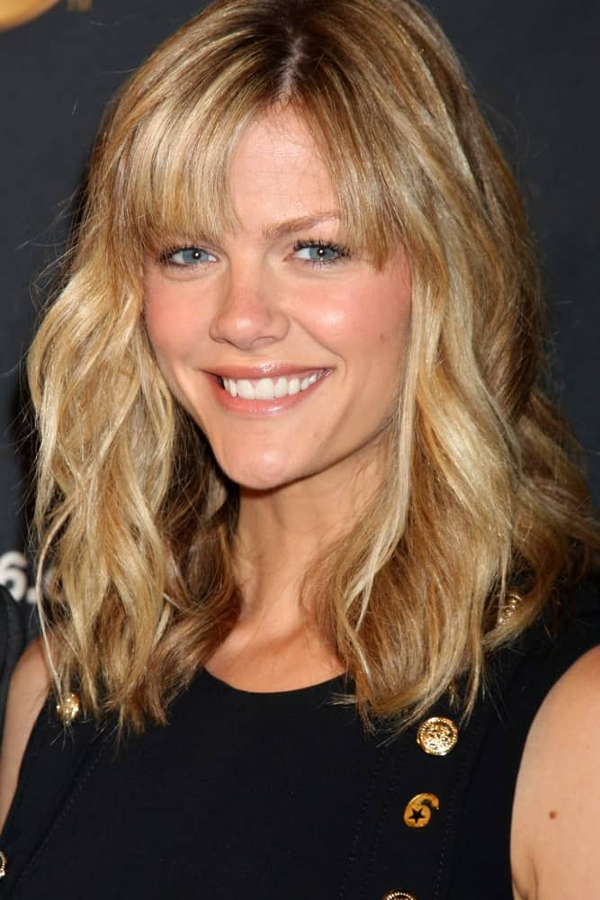 Bangs are always a really cute look and go well with short blond hair. Shoulder-length wavy hair looks great on just about anyone and when paired with bangs, it can create a really wholesome look.