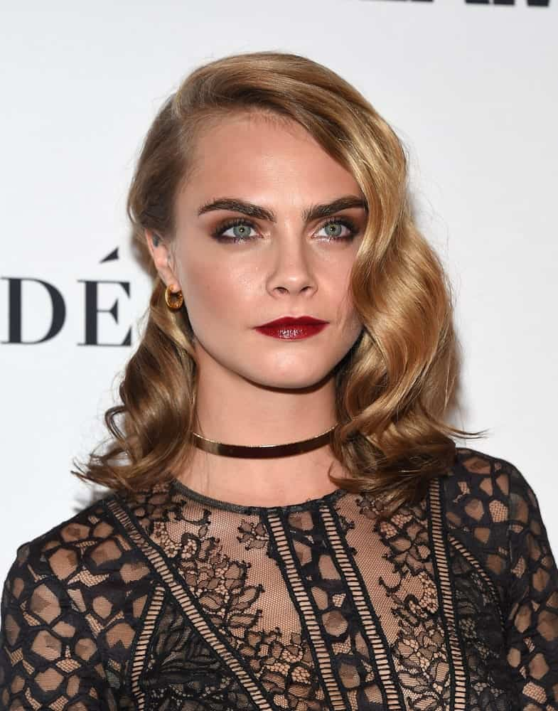 "If you are a fan of ""out-there"" kind of hairstyles, perhaps Cara Delevingne has given you the perfect one. This hairstyle has a side parting with hair from one side pinned behind the ear and from the other side; you see waterfall-like waves falling on the face graciously. Towards the end the waves turn into rounded curls that simply look beautiful."