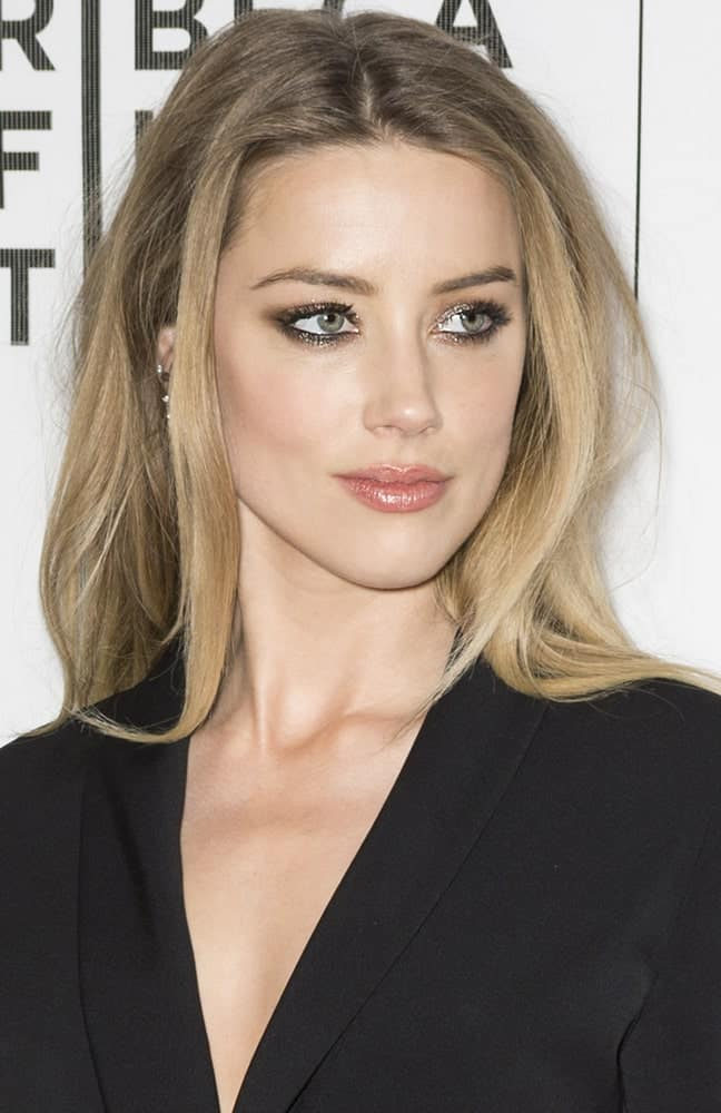 Amber Heard looks simply stunning with her dark blonde hair that has been thrown towards the back with just a few strands left in the front. The hair has been parted in the middle to add some volume and elevation to the overall look.