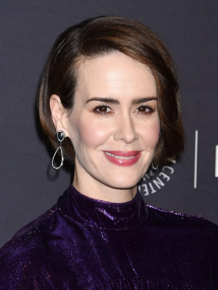 All those who love super straight and ultra-sleek hair will absolutely love this hairstyle. Sarah Paulson looks beyond amazing in this smooth and shiny bob that consists of long, side-swept layered bangs that call for attention, given their gentle change of hues. It has a clean side parting where the hair from one side has been tucked behind the ear while the other side has been set free in front to caress the face mildly.