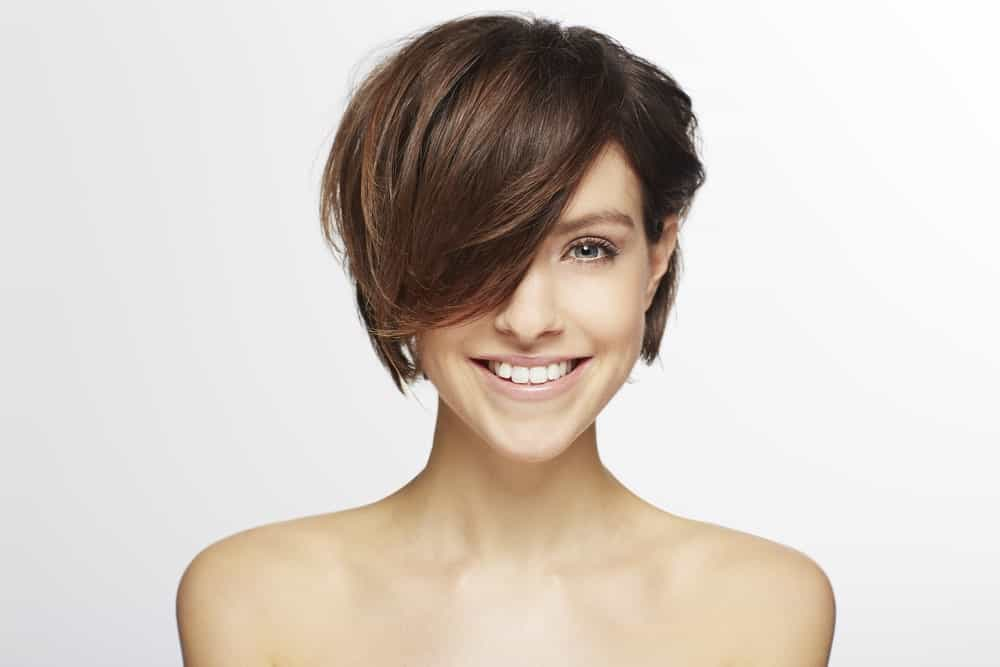 This is a super chic and unique hairstyle that is similar to a pixie-cut, except that a thick, sleek lock of hair is falling on the face on one side and from the other side; the hair has been pinned behind the ear.