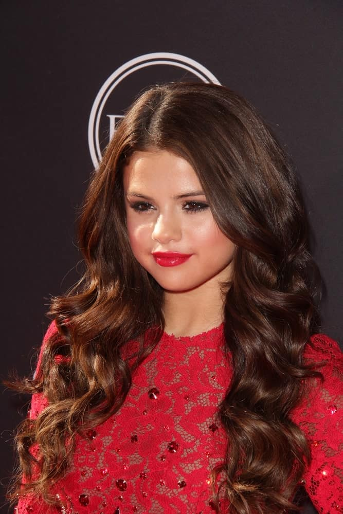 Over the years since she made her first appearance, this young singer has shown her fans that there are countless ways to rock a curly hair type. Here we see the pretty Selena Gomez look stunning with beach waves flowing down from her half-straightened hair. A brief touch of highlights is a good way to accentuate the loose locks.