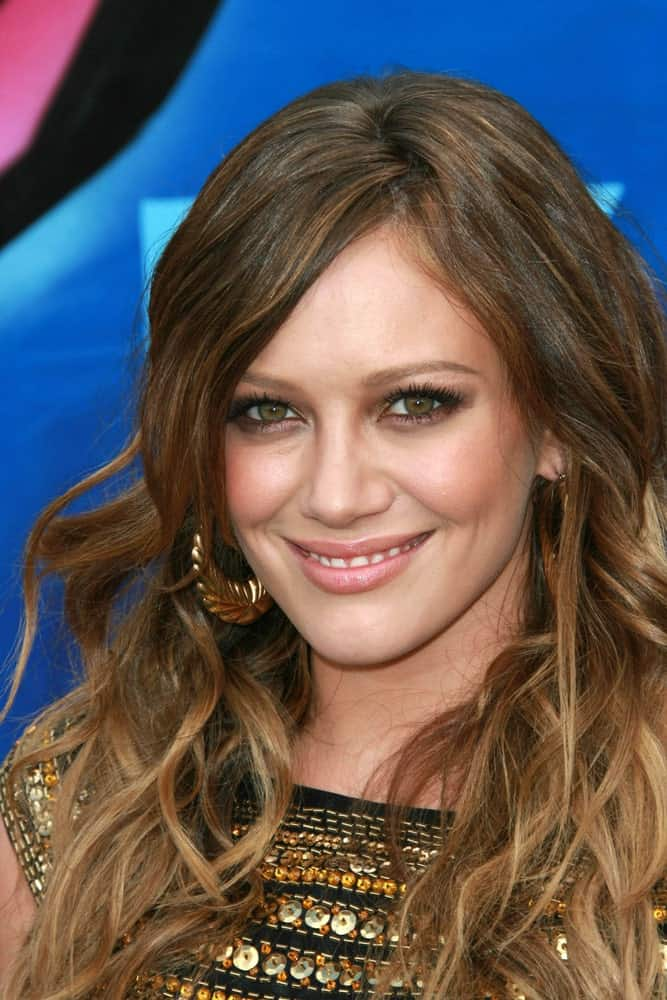 Wispy tousled strands that feature a spectrum of brown and dull brown shades make Hilary Duff look chic in this trendy hairstyle for women with curly hair.