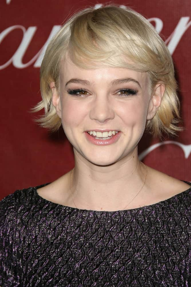 This minimalistic layered bob is worn by the stunning Carey Mulligan where her hair has been cut into feathery strands at ear-level.A similar approach to finishing the short baby bangs together give her a youthful and playful look.