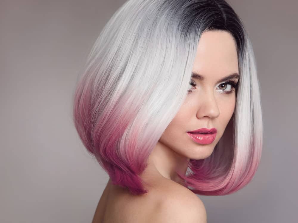 For all those who love to experiment with their hair and have a knack for going big and bold, this is the perfect look for you. This style of highlights has been divided into three sections where the top section has jet black hair, followed by ashy silver-white hair, and then finally, hues of soft pink throughout the bottom. The short bob makes it look even more stylish and funky!