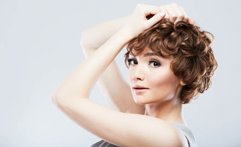 This is a super short curly hair-do that looks quite chic and stylish. The hair from the back seems to be less curly, and the front portion has deeply rounded curls that look fresh and bouncy.