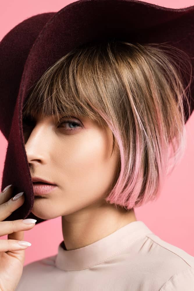 If you love funky looks and styles, you ought to get these highlights done. This is a super short, sleek bob with light golden-brown highlights at the top followed by shades of pink at the bottom.