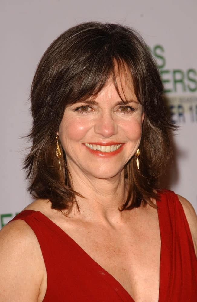 Here we see Sally Field looking a lot younger than her actual age just by wearing her hair in free-spirited layered bob hairstyle. Curtain Bardot bangs gently cover the forehead, avoiding a plain and bare look whereas the feathery tips give a regal touch.