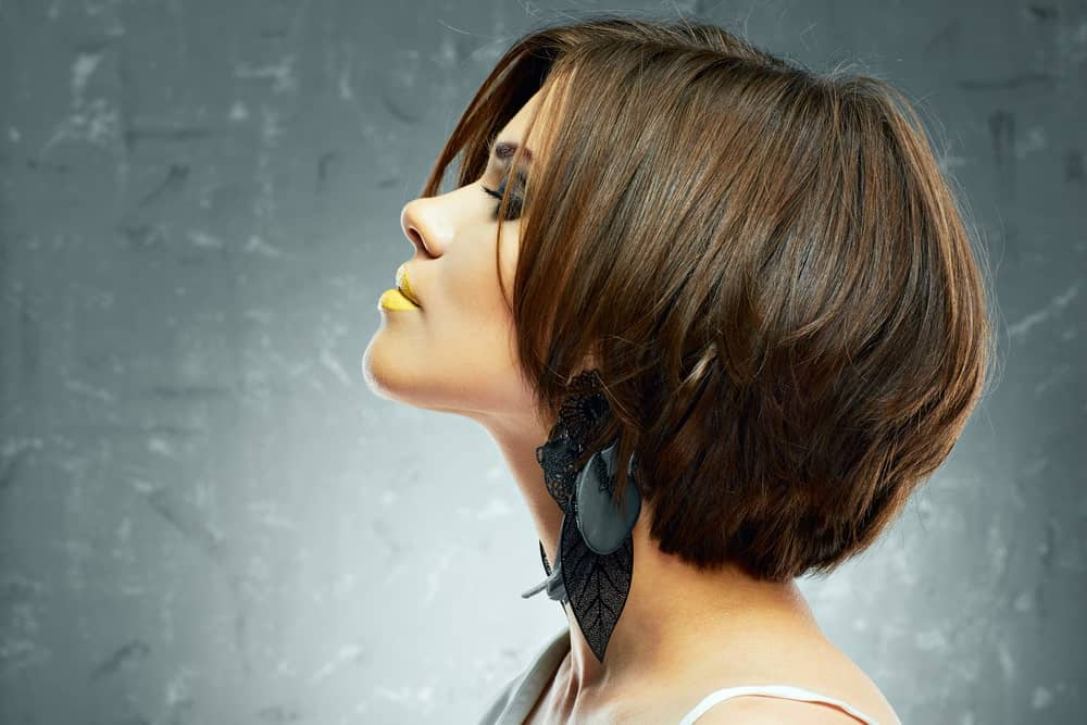 This is an absolutely breathtaking short hairstyle with a lot of layers of short hair on top of each other that are super straight, sleek and glossy. The hair length is till the nape of the check which is what really that gives it the edgy kind of a look.