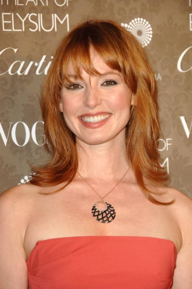 Alicia Witt sports a great short red hairstyle for women by going for a feathered cut coupled with eye-skimming, airy separated bangs. Slightly curl the ends into outward whirls for a fancier finish.