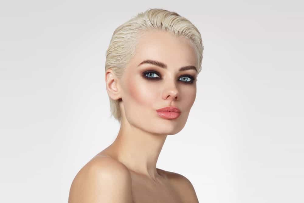 Ask your stylist to color your hair a brilliant platinum-blonde and cut it into a super-short pixie style, which parts on the side. Use some mousse to make your hair lie flat in an elegant and effortless style.