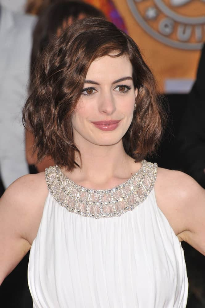 Anne Hathaway looks like the epitome of beauty and grace is this hair style. This is a slightly longer bob with a side parting and hair that has been transformed into slightly messed, ruffled waves-like curls that anyone can pull off effortlessly.