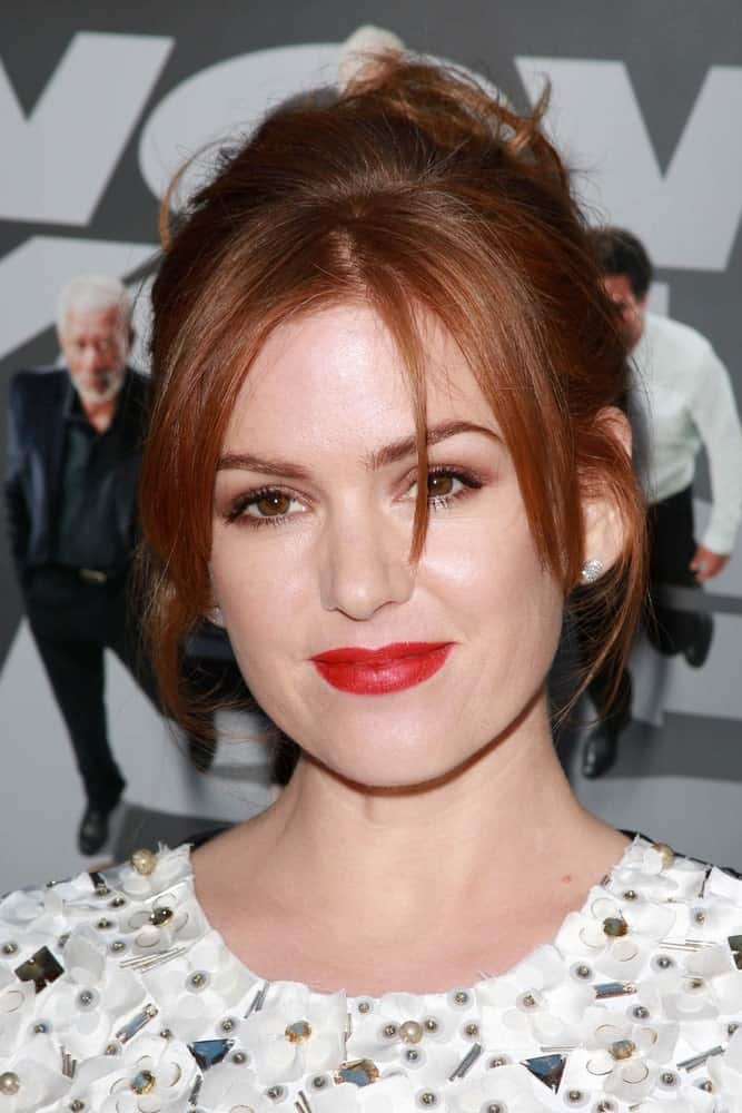 This short red hairstyle for women is oozing beauty and style. With hair pulled up in a neat bun, Isla Fisher lets sleek and silky bangs adore her face to evoke an aura of grace and elegance.