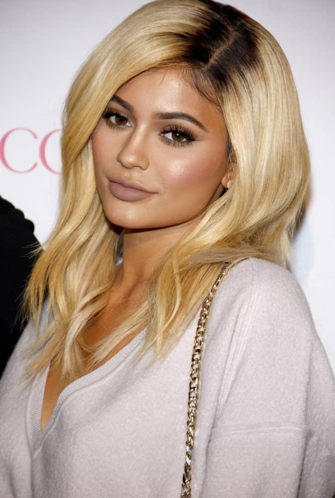 Since dyed hair is relatively common, most of us seamlessly follow the trends, experimenting with highlights, lowlights, balayage, and what not! Kylie seems to be doing the same, experimenting with light hair and dark roots! While it is definitely a rather unique hairstyle, it still looks perfect.