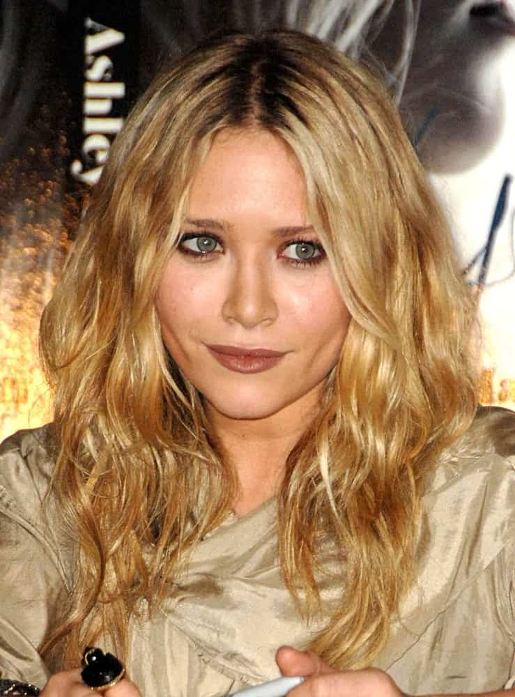vThe golden hair helps accentuate the messy tousled hairstyle. They create a really nice look since the soft waves in the hair frame the face perfectly.