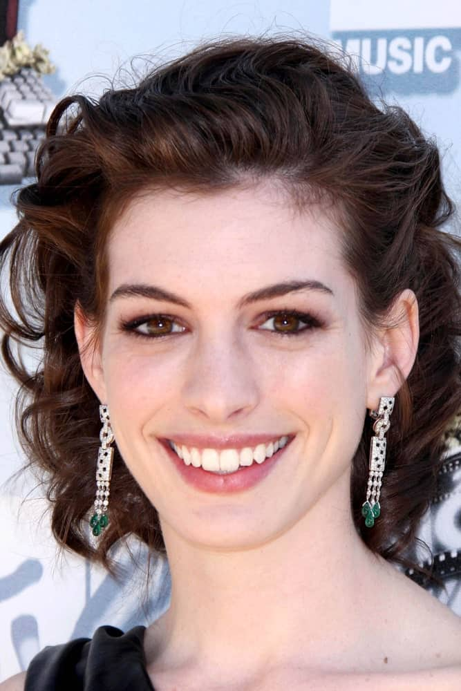 Anne Hathaway is the epitome of beauty and grace, and that's exactly how she looks here with her absolutely chic and short curly hair up-do. She seems to have come right out of a 90s magazine with this fashionable hairstyle. The hair from the front has been swept all the way back followed by twisted, knot-like curls that look wonderful. Anyone with a chiseled face structure will absolutely rock this curly look!