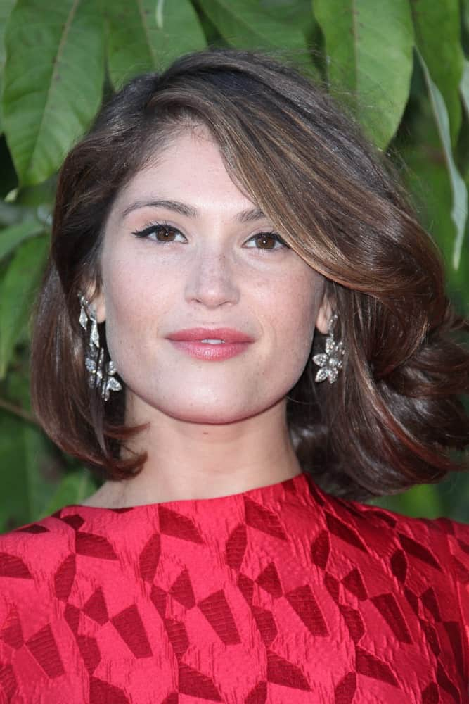 Gemma Arterton takes the classic short bob to a whole new level with her unique touch to a simple hairstyle. Her hair seems blow-dried, which gives the hair significant volume, texture, and a bouncy appearance. There are also different layers in the hair that gives it a ruffled look.