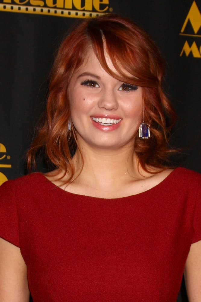 This short red hairstyle for women features a chin-length cut. Notice how Debby Ryan manages to let the beauty of red hair shine even in a short length by sporting thick bangs at the front.
