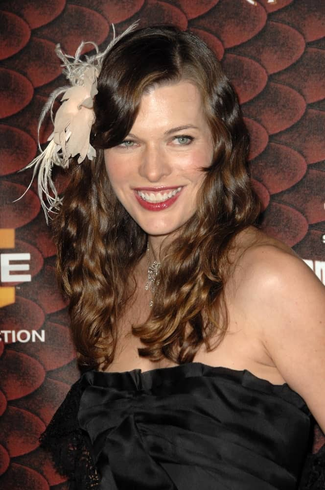 This style is usually the go-to option for many women with curly hair who want a slight touch of silky straightness yet don't want to part with their naturally curly hair altogether. Milla Jovovich has flattened just the hair at the top while letting the rest as it is. Clipping the bangs to the side in this retro style gives a nod to the old world charm.