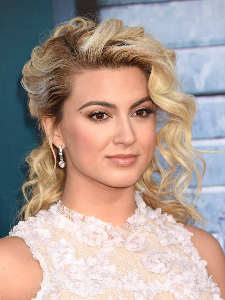 For those who wish to do something different with their hair than simply letting it loose should go for this pretty hairdo worn by the amazing Tori Kelly. This hairstyle has a big chunk of hair in the front that has been curled into big curls. The rest of the hair also has big, voluminous curls that have been gathered towards the back and tied half-way. This is simply a unique and uber-chic hairstyle.