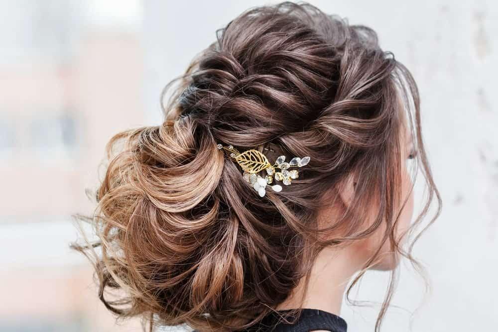 "This is one of those ""messy"" looks that are impossible not to like. The balayage brings out the best of the brunette hair as it is styled at the back in a rather fancy bun. In the front, the hair is twirled towards the back and adds to the bun while a few loose strands complete the look by perfectly framing the face."