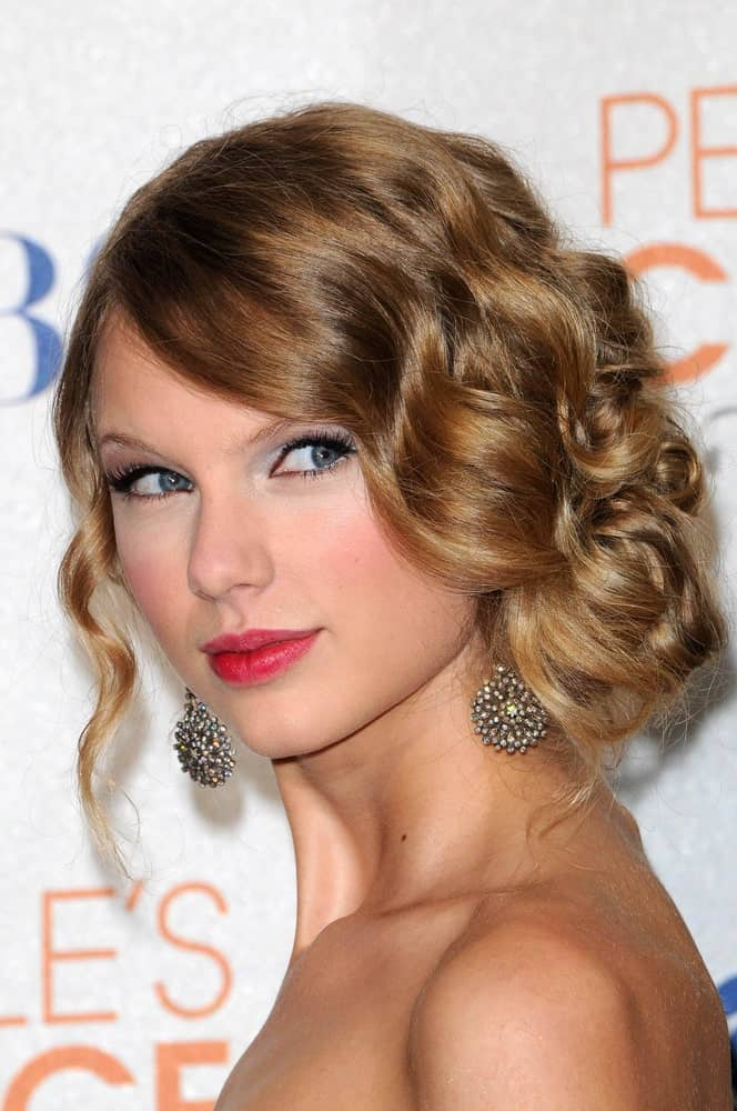Taylor Swift's sophisticated wedding hairstyle is swift and easy to recreate because all it requires is a bit of excessive curling before twirling the tousled strands into a loose low bun at the side. Let a sole strand hanging on the other side to balance the one-sided bunch.