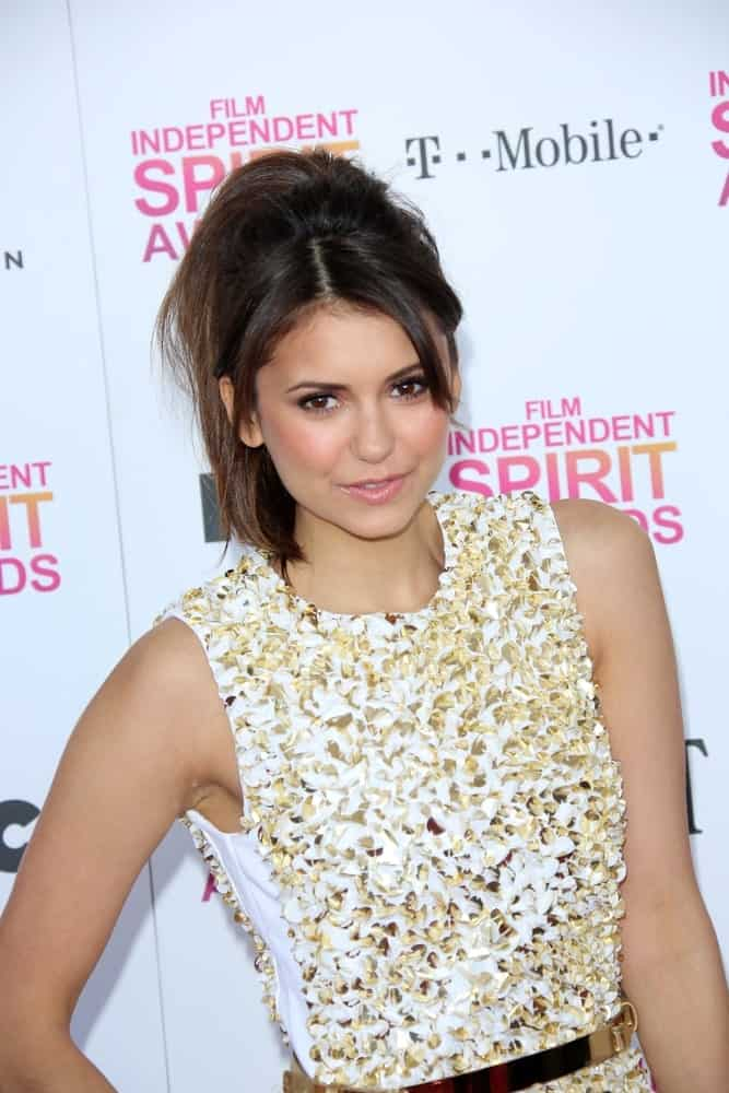 Nina Dobrev's upward hairdo balances casual and elegant just perfectly. The fluffy ponytail gives her a lively, young and playful look whereas the side-part coupled with short bangs are the ideal way to frame a heart-shaped face profile.