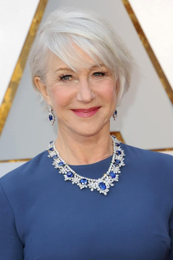 This elegant gray hairstyle for women is suitable for older women as well as younger ones who are considering coloring their hair to pale white or platinum gray hues. Helen Mirren looks dazzling displaying her snowy white hair in an angular bob that is accentuated by wispy, side-swept bangs.
