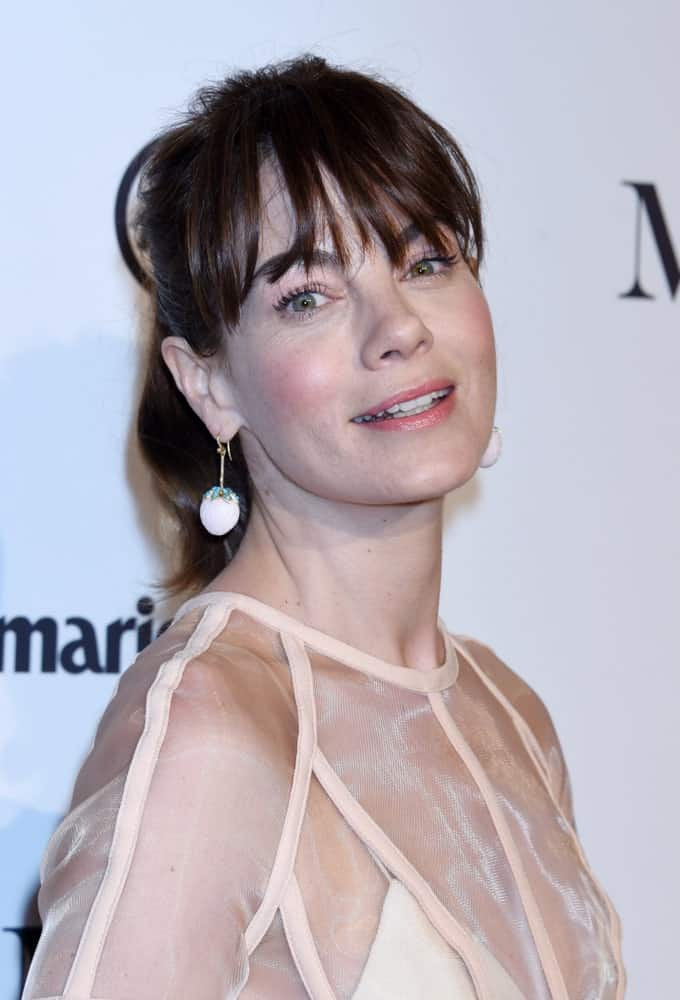 Michelle Monaghan appears far younger than her actual age when sporting this lose ponytail accompanied by deep eye-skimming and airy-separated bangs. A loose hairstyle like this one gives you a bubbly and sporty image.