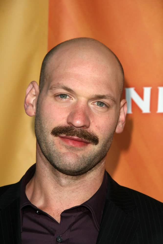 Corey Stoll has never looked better than in this classic clean head, except with slight hair on the sides coupled with a prominent chevron mustache! The icy blue-green eyes with shades of grey and that slightly darker facial scruff take the entire look to a whole new level.