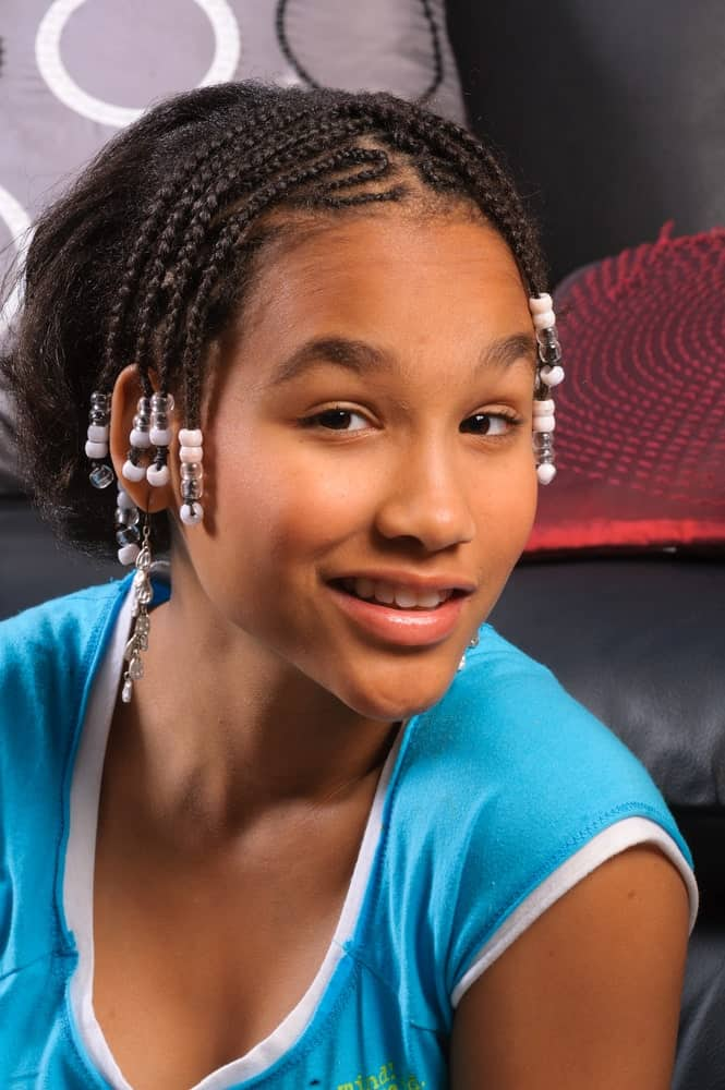 You don't necessarily need to have long hair or add extensions to get the Fulani braid look. Do as this young girl did. Simply add a few locks of cornrows on the front and side of your head and embellish them with pink and white beads. Leave the back part of your hair loose and natural. This style is very quirky and age-appropriate for young girls.