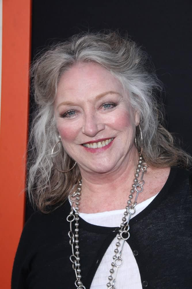 This 'organic' hairstyle sported by Veronica Cartwright is au naturel in every sense. Not only do we see the patches of gray in her dull brown hair, but she hasn't spent much time in styling it either. Instead, she has simply clipped back a few locks to create this easy-going half-up-half-down hairstyle that looks impressive despite the simplistic approach.