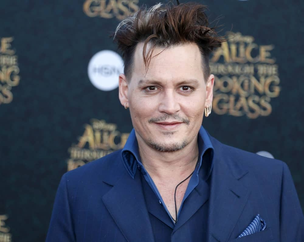 """Known for playing eccentric, and often times, dark roles, Johnny Depp often displays his unconventional tastes with his choice of apparel and hairstyle. Here, """"The Fantastic Beasts"""" actor's barber has styled his thick hair into gelled-up and slicked back spikes. He has also give Depp an edgy-looking forelock. The style is very unusual but fits Depp very well. For those who are not afraid of edgy, out-of-this-world styles, this slicked-back style is a masterpiece."""