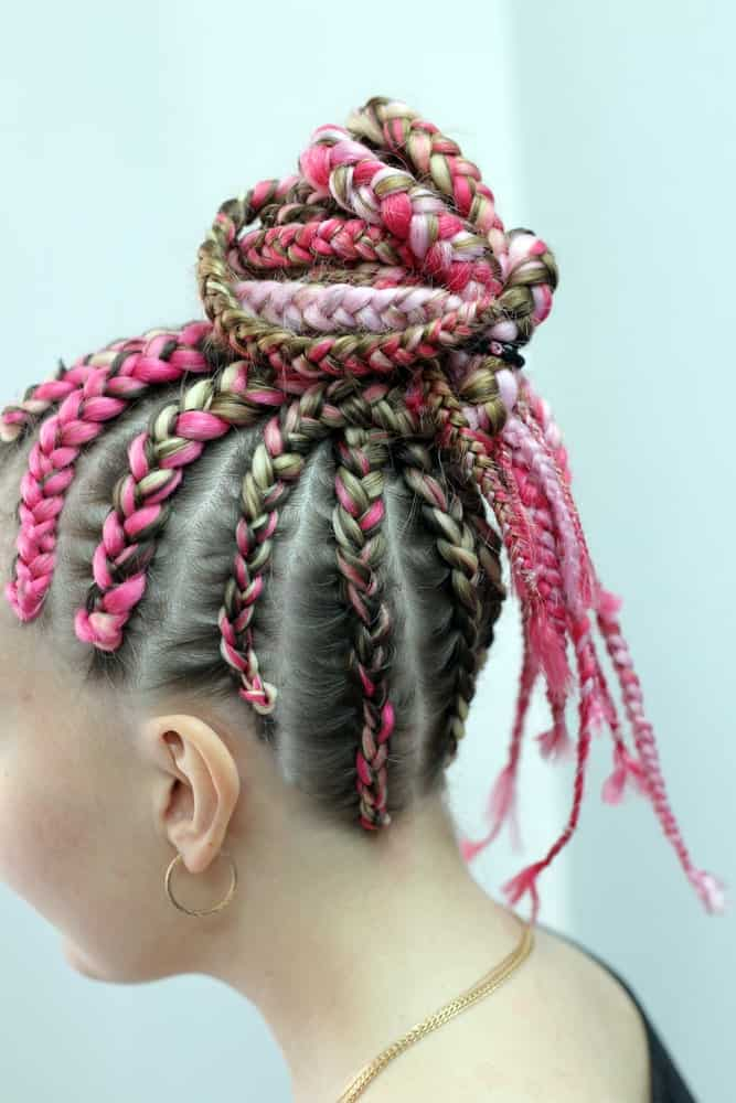 Pink is the color of the Millennials so why not incorporate it into your hair as well? For a more statement look, ask your stylist to paint your hair in various hues of pink instead of just one shade. Then add more pink thread and weave your hair into simple Fulani braids. To keep your dangling locks away from your face, twist them into a cool topknot.