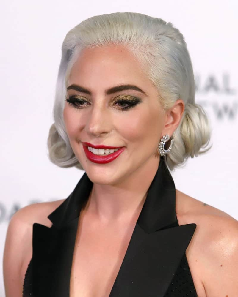 Vintage fashion in all its glory takes center stage with Lady Gaga's retro-themed gray hairstyle. Featuring a subtle side-part in a brushed back style and a bobby pin to hold back the short locks behind the ear, this neat and tidy hairstyle is a gentle nod to the old-world charm.