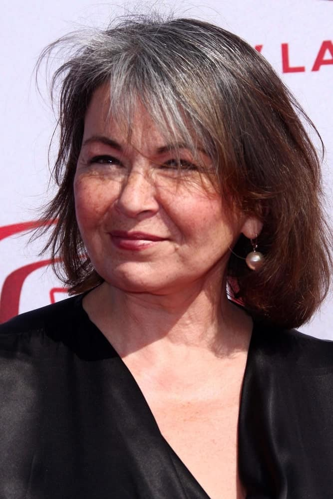 Roseanne Barr provides a useful hairstyle for women whose hair have begun graying only at the front. And the trick is to go for thin and fine bangs that bring out the silvering hues because it will contrast well against your dark hair and thus, call attention on its own.