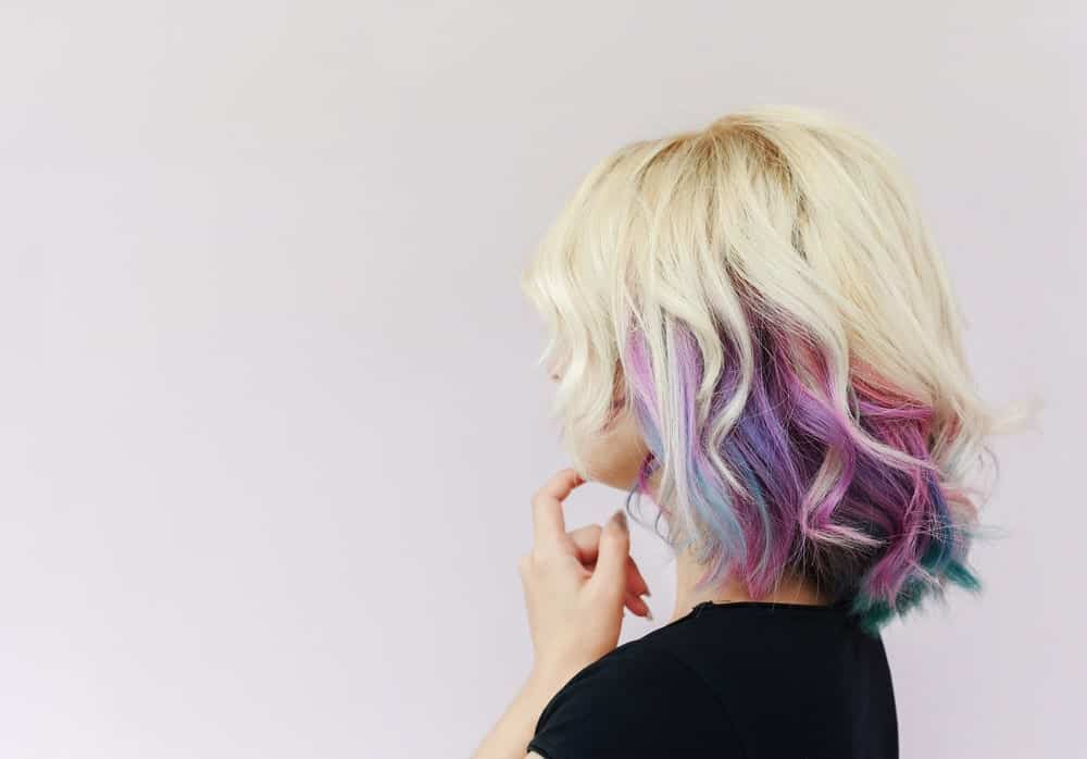 Here is another one of the rainbow hair looks! This time, however, the soft pink and purples are paired with the darker, edgier hues of blue and green colors. With a choppy lob, this gives the model a slightly edgy look.