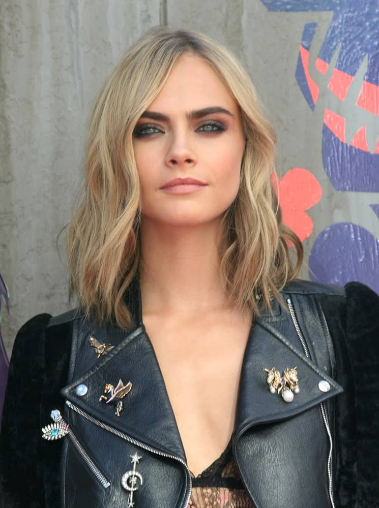 Cara Delevingne is always effortlessly cool and collected. The actress looks great whether she wears her hair in its natural dark color or goes for a lighter shade. Here, the supermodel is rocking a honey-blonde balayage chopped off at the shoulder-length. She gave her hair an off-center parting and added some texture to her locks to give it a messy and edgy look. To get the look, casually bend the hair from the mid-length with a curling iron. Paired with her black leather jacket, the look is super cool and works to enhance the model's cheekbones.