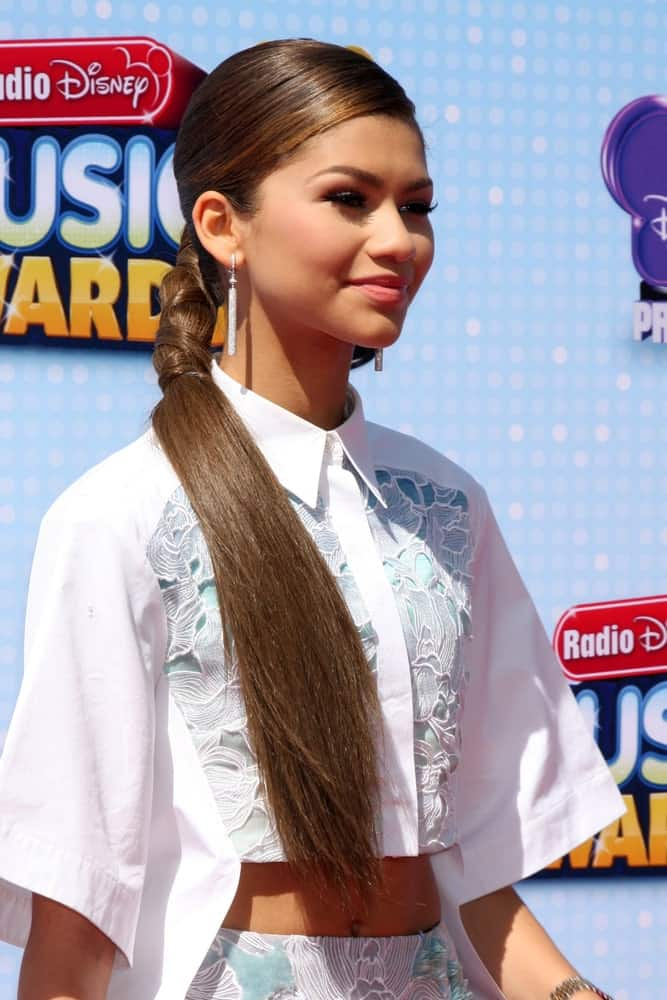This ponytail hairstyle for women sported by the young and popular Zendaya features her single-shaded hazelnut brown hair tied in a really unique and fascinating manner. Although the ponytail itself isn't particularly unique, what makes it distinct are the rubber bands that she has tied in a crisscross style.