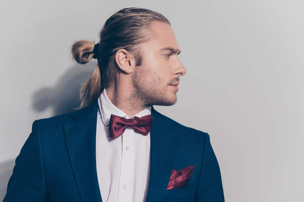 Do you know you can rock a man bun with a tuxedo? Just check out this great style. This model has his long hair slicked back from his forehead and tied back in a half man bun. Note that only the front of his hair is gelled back. The hair in his ponytail and down his back has minimal product, which gives this style balance and keeps thing both casual and sophisticated at the same time.